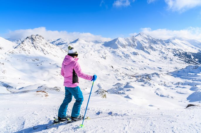 Young woman skier standing on ski slope and looking at snowy mountains in Obertauern, Austria shutterstock_566198236