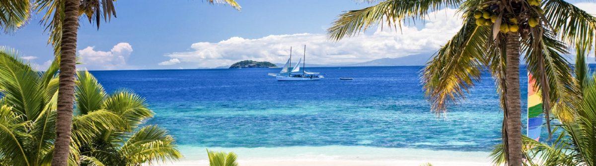 Sail boat seen through palm trees, Mamanuca Group islands, Fiji iStock_000035487092_Large-2