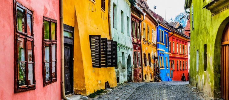 Sighisoara, Romania. Stone paved old streets with colorful houses in Sighisoara fortress, Transylvania region of Europe shutterstock_386883811-2