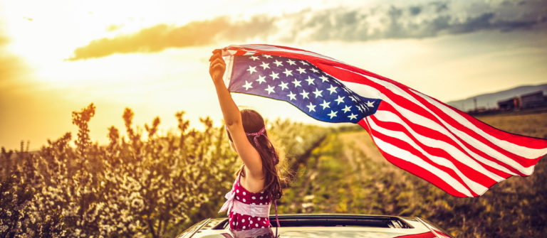 Girl Through a Car Sunroof Waving with USA Flag