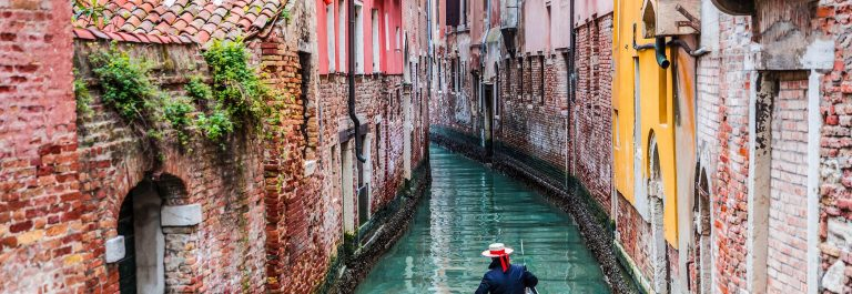 Venetian gondolier punting gondola through green canal waters of Venice Italy shutterstock_267588308-2
