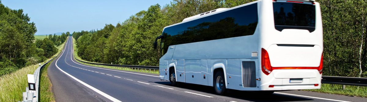 White Bus driving along an empty asphalt road lined