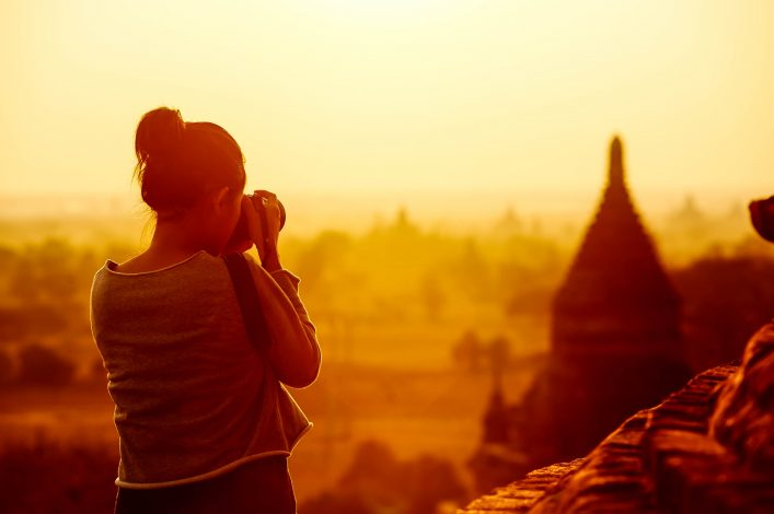 female traveler photographing temples at Bagan Myanmar Asia at sunrise shutterstock_134373716-2