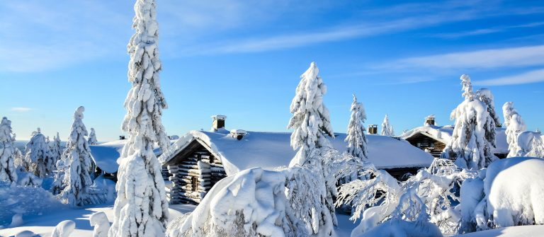Cottages on snowy mountain on a sunny winter day
