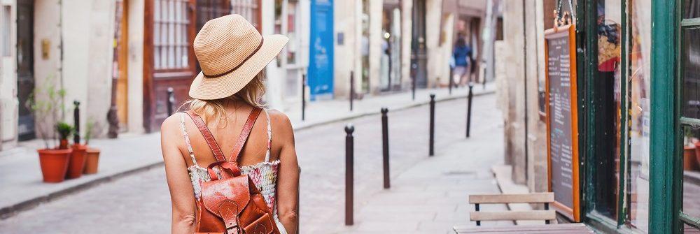 Woman walking through Paris France shutterstock_427200133_1000px