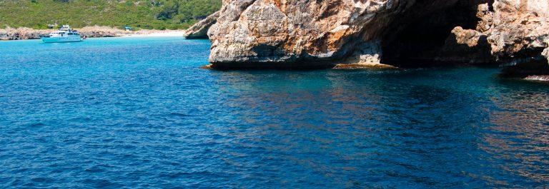 Natural arch and recreational boat at Cala Antena, Majorca island, Spain shutterstock_54519319-2