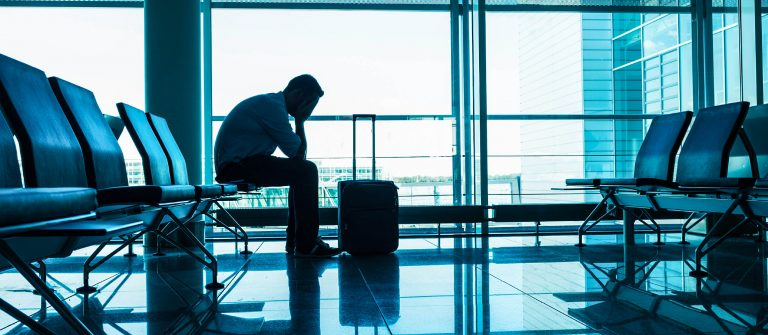 Unhappy passenger waits for flight at airport iStock_000071225575_Large-2