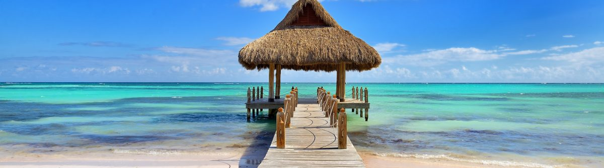 Tropical white sandy beach. Palm leaf roofed wooden pier with gazebo on the beach. Punta Cana, Dominican Republic shutterstock_583369816