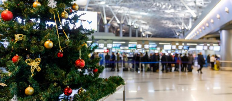 Christmas-tree-in-the-airport-and-people-at-the-check-in-counters-in-the-background-shutterstock_634633655