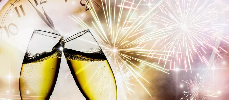 Glasses with champagne against fireworks and clock close to midnight shutterstock_122288275-2