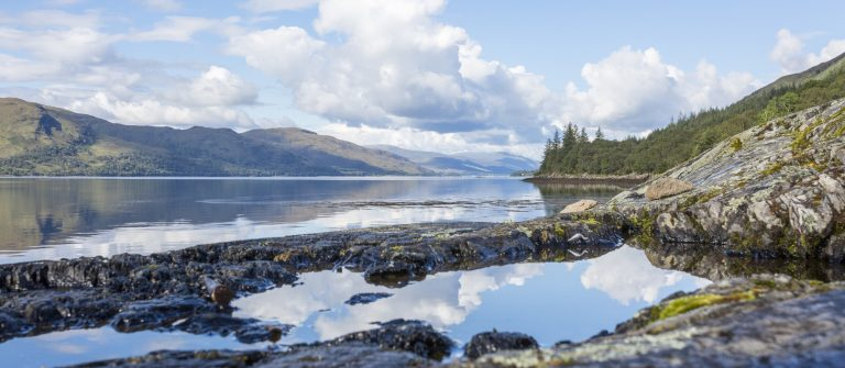 Loch Eil in the Scottish Highlands. Lake with trees, reflections and blue sky_shutterstock_711005494_klein