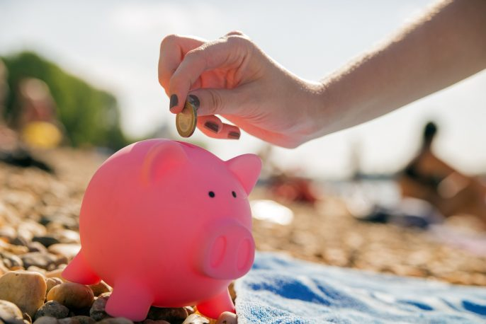 Putting coin into piggy bank , Holiday savings