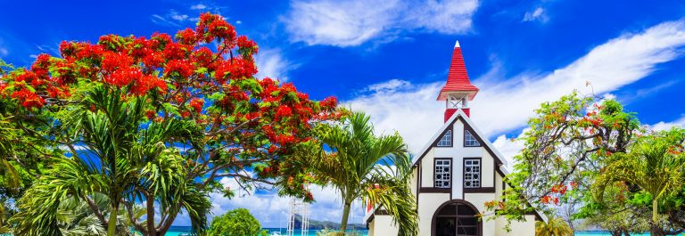 Scenery of beautiful Mauritius island – Red church on the beach with blooming flamboyant tree.