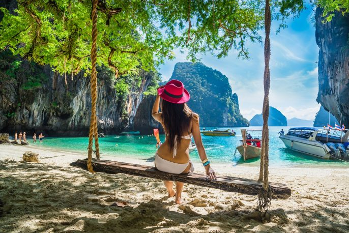Beautiful woman in bikini sitting on wooden swing under tree and looking destinations beach, Koh Lao Lading island, An_618044864