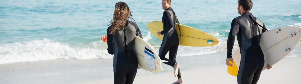 Group of friends on wetsuits with a surfboard on a sunny day at the beach_281813564