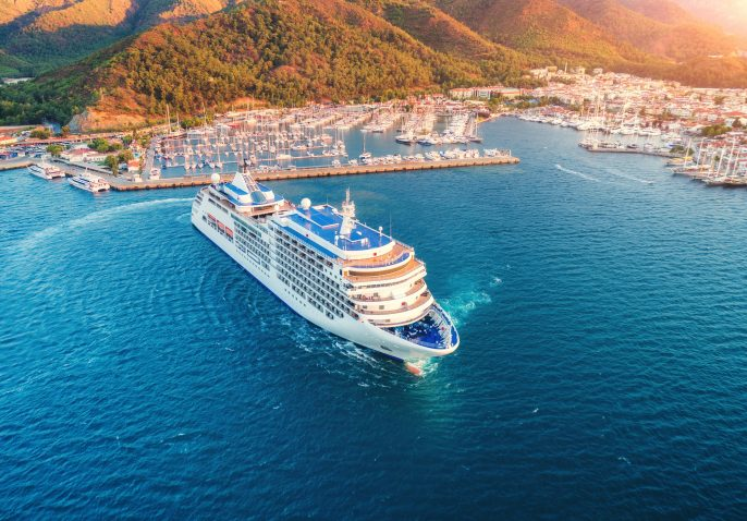 Cruise-ship-at-harbor.-Aerial-view-of-beautiful-large-white-ship-at-sunset.-Landscape-with-boatsResort_1074480827