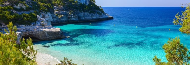 Secluded beach with turquoise sea water, Cala Mitjaneta, Menorca island, Spain shutterstock_189270002