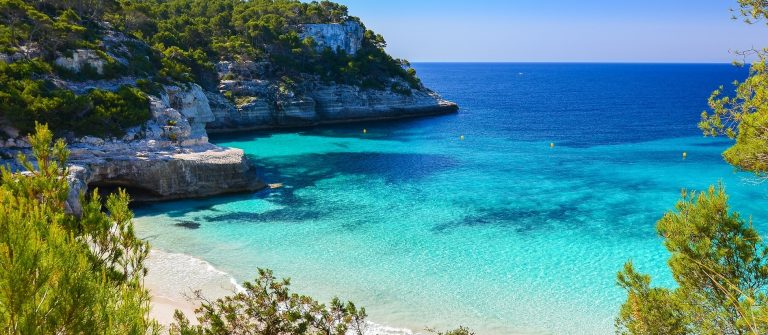 Secluded beach with turquoise sea water, Cala Mitjaneta, Menorca island, Spain shutterstock_189270002