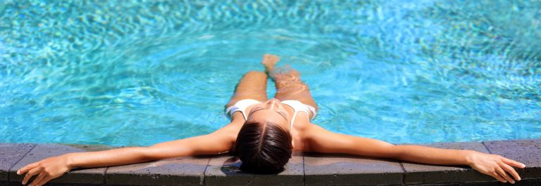 Bikini woman lying relaxing in infinity pool at luxury resort spa retreat shutterstock_503082934