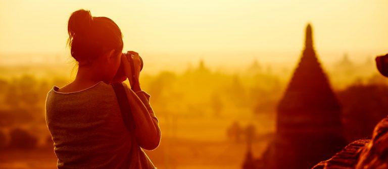 female traveler photographing temples at Bagan Myanmar Asia at sunrise shutterstock_134373716-2