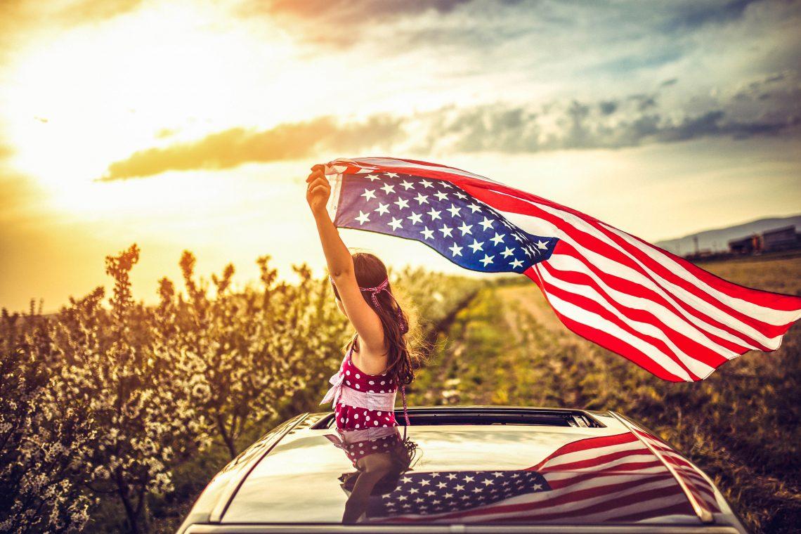 Girl Through a Car Sunroof Waving with USA Flag