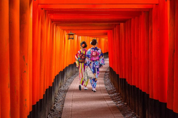 Women-in-traditional-japanese-kimonos-walking-at-Fushimi-Inari-Shrine-in-Kyoto-Japan_550609591
