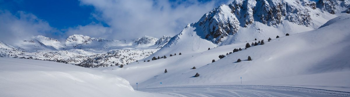Fresh-ski-slope-and-mountains-in-sunny-day_shutterstock_200674709
