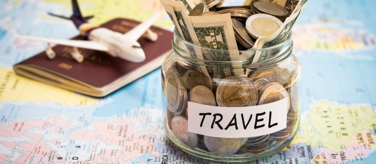 Travel budget concept with compass, passport and aircraft toy