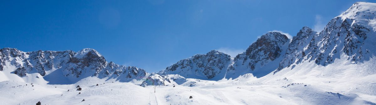 lots-of-skiers-sliding-down-the-slope-with-high-mountain-peak-on-the-background_shutterstock_208472077