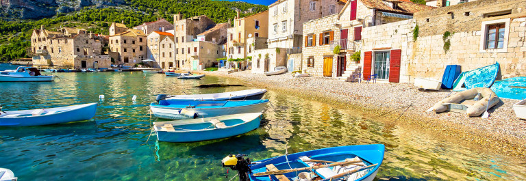 Scenic beach in Komiza village waterfront, Island of Vis, Croatia shutterstock_339335786-2