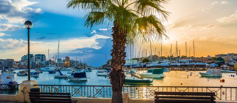 Beautiful sunrise with benches, palm tree and sailboats at Sliema bay, Malta shutterstock_357393446-2