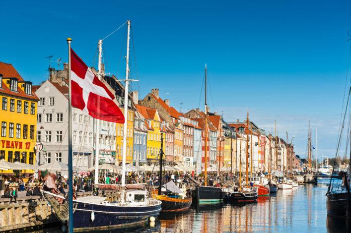 Copenhagen Danish flag flying over Nyhavn colourful harbour