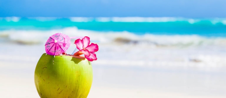 fresh coconut cocktail on tropical beach with flower