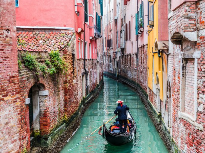 venetian-gondolier-punting-gondola-through-green-canal-waters-of-venice-italy-shutterstock_267588308-2